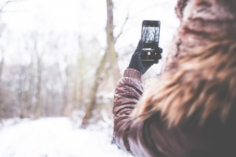 Mujer que toma la imagen de bosque nevado