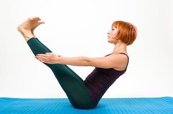 Yoga posando sobre un fondo de estudio gris