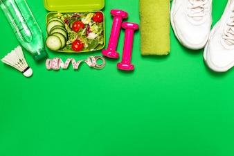 Zapatillas de deporte con una ensalada y pesas rosas