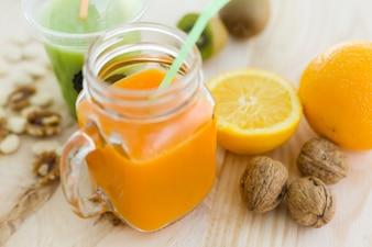 Zumo de naranja en vidrio, nueces y frutas frescas en backgroun de madera