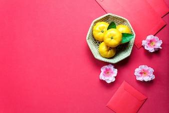 Accessori di vista superiore Decorazioni cinesi del nuovo anno festival, foglia, cestino di legno, pacchetto rosso, fiore di prugne su sfondo rosso.