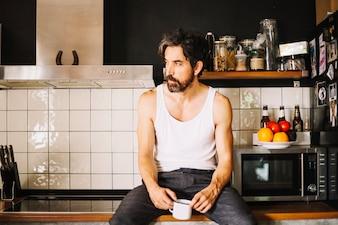 Adulto uomo bello che sogna in cucina