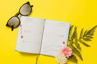 Agenda con occhiali da sole e fiori