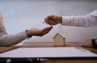 Agente immobiliare che dà chiavi al cliente dopo la firma del contratto.