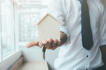 Agente mano con casa in palma e chiave sul dito.