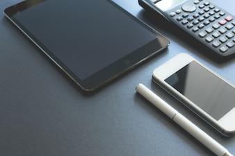 Alcuni dispositivi elettronici visualizzati su sfondo grigio. Smart phone, pad e calcolatrice, tutto digitale tranne una penna. Posto di lavoro di scena.
