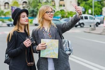 Allegri amici di sesso femminile che prendono selfie
