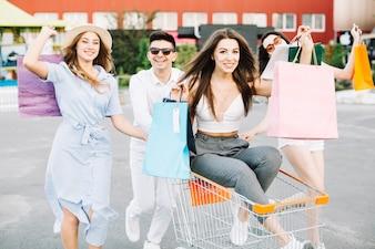 Amici che guidano carrello di acquisto