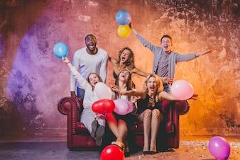 Amici felici con palloncini al divano