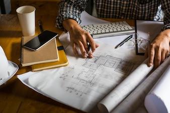 Architetto creativo che proietta sui grandi disegni nell'ufficio o nel caffè scuro dello sgabello con stile scuro e retro.