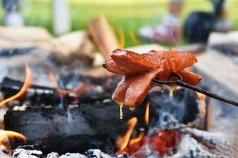 Arrostire le salsicce sopra un fuoco. Campeggio in natura - cibo.