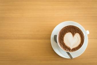 Arte calda latte caffè in una tazza sul tavolo di legno