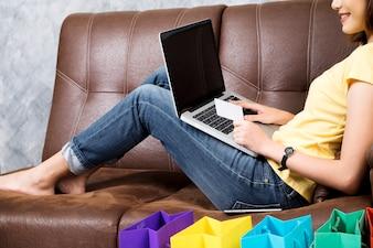 Asia donna shopping online a casa. Cercare il prodotto nel sito web di acquisto e pagare con carta di credito.Copyspace online shopping e prodotto di consegna a casa concetto.