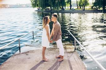 Baciare coppia in piedi sul molo