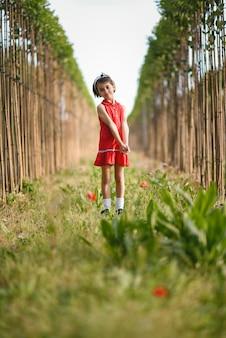 Bambina che cammina nel campo della natura che porta vestito bello