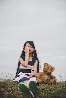 Bambina seduta con il suo orso sconvolto nei prati campo.