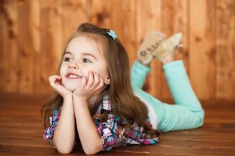 Bambina sognante si trova sul pavimento in legno e tiene il mento sulle palme