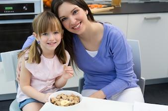 Bambino che mangia cereali con sua madre in cucina