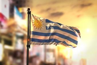 Bandiera Uruguay Contro La Città Sfocata Di Sfondo Al Retroilluminazione Di Alba