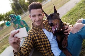 Bel giovane con il suo cane utilizzando il telefono cellulare nel parco.