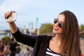 Bella donna urbana presa fotografia di se stessa, selfie. Immagine filtrata.