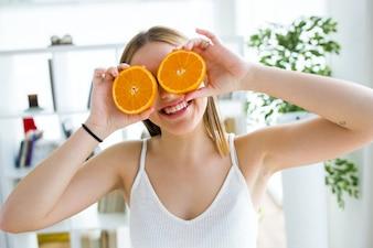 Bella giovane donna che gioca con frutti arancioni.