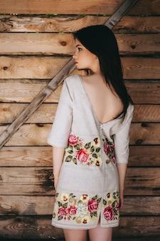 Bella giovane donna che indossa nazionali vestiti ucraini in capanna di legno