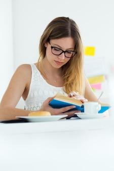 Bella giovane donna che legge un libro e che ha colazione a casa.