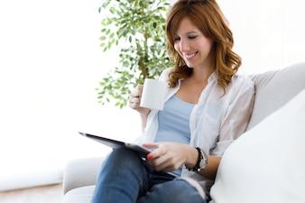 Bella giovane donna che utilizza la sua compressa digitale a casa.