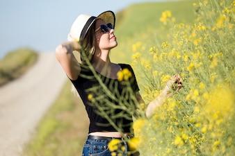 Bella giovane donna con fiori godendo estate in un campo.