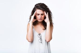 Bella giovane donna con mal di testa su sfondo bianco.