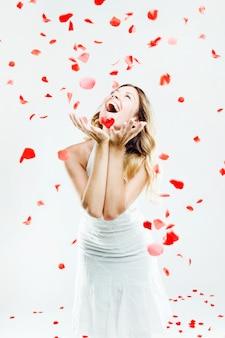 Bella giovane donna sotto una pioggia di petali di rosa. Isolato su bianco.