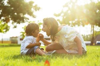 Bella giovane madre con il figlio che mangia yogurt nel parco.