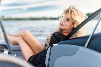Bella ragazza bionda distesa su uno yacht e guardando la fotocamera