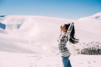 Bella ragazza godendo il sole, giorno d'inverno in montagna