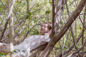 Bella ragazza in posa sdraiato su un albero