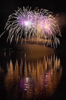 Bellissimi fuochi d'artificio colorati sulla superficie dell'acqua con uno sfondo nero pulito. Festival di divertimento e concorso internazionale di vigili del fuoco provenienti da tutto il mondo Ignis Brunensis 2017. Diga di Brno - Repubblica Ceca.
