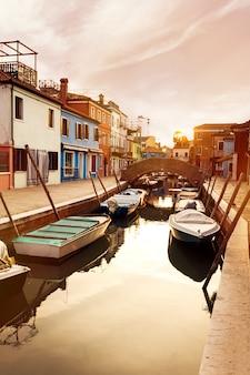 Bellissimo tramonto con barche, edifici e acqua. Luce del sole. Tonificante. Burano, Italia.