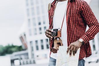 Bello e felice turista afroamericano con la vecchia macchina fotografica e la mappa nella città moderna