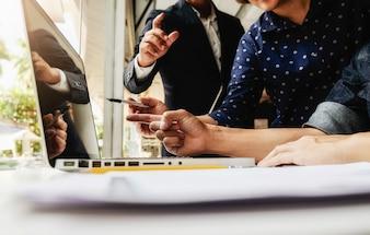 Business manager aziendale asiatico analizzando il dato in grafici e digitando sul computer, appunti in documenti sul tavolo in ufficio, colore vintage, fuoco selettivo. Concetto di affari.