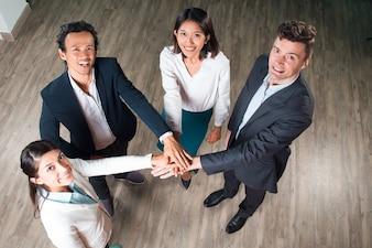 Business team felice con le mani insieme in sala