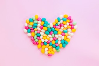 Candy cuore colorato sul tavolo rosa