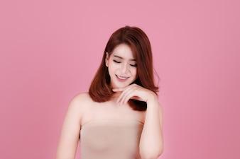 Capelli corti asiatico giovane donna bella sorriso e punto sulla sua testa, isolato su sfondo pastello rosa. trucco naturale, terapia SPA, skincare, cosmetologia e concetto di chirurgia plastica