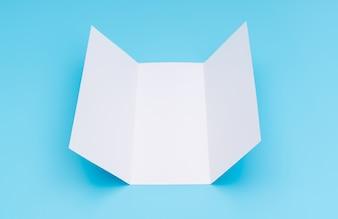 Carta di modello bianco trifold su sfondo blu.