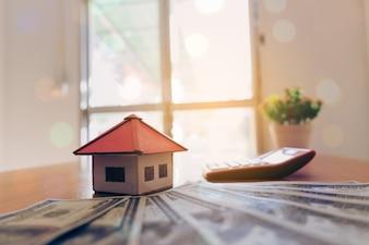 Casa dalla carta e denaro su fondo in legno