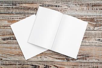 Catalogo in bianco, riviste, libri su sfondo di legno.