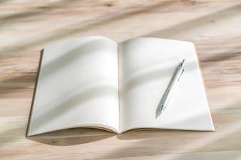 Catalogo in bianco, riviste, libro mock up con penna su sfondo di legno.