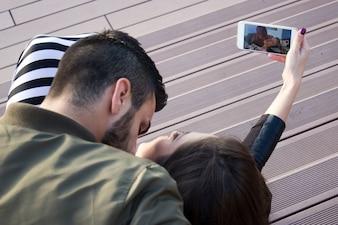 Cattura momenti luminosi. Giovane coppia felice allegra facendo selfie sulla fotocamera mentre è in piedi all'aperto.