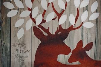 Cervi rossi con foglie bianche dipinte sulla tavola di legno