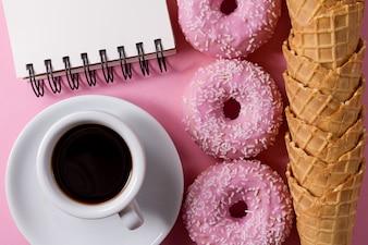 Ciambelle fresche gustose fresche con crema di gelato coni caffè e taccuino su sfondo rosa.